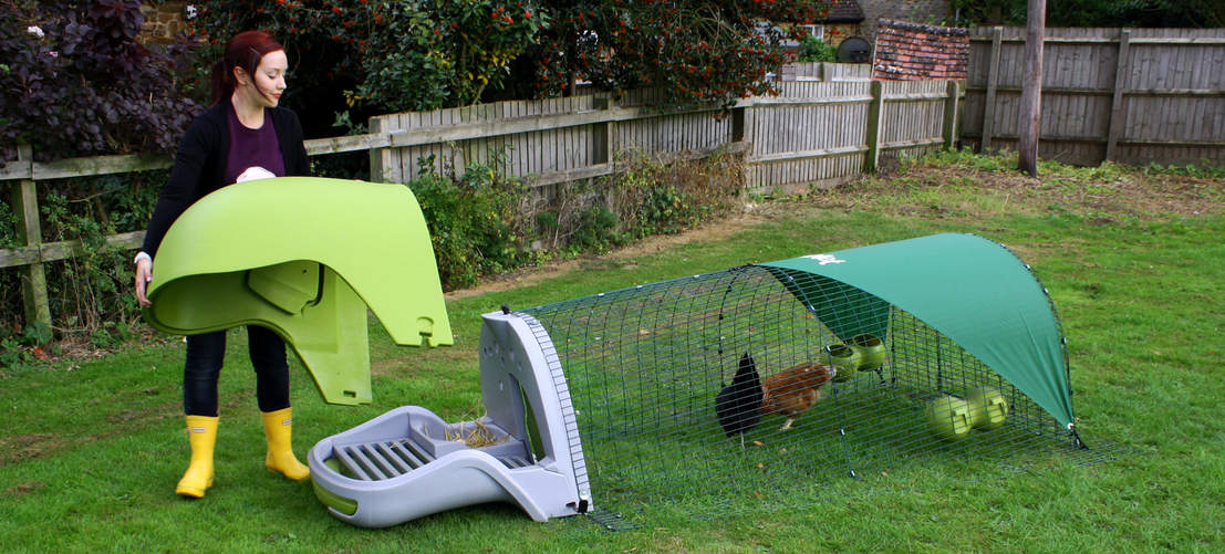Eglu Classic plastic Chicken Coop with run - girl removing Eglu lid