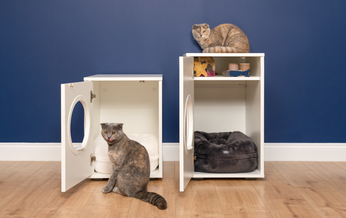 Two cats with the maya modern cat house doors open showing the cat house storage