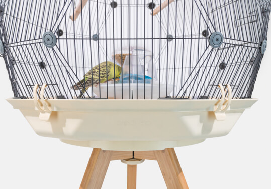 The Geo Bird Cage on a wooden stand with a cream colored base