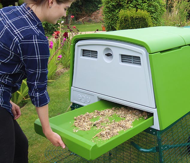 A woman sliding out the plastic dropping tray of a modern chicken coop